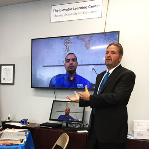 Bob Schaeffer demonstrating distance learning at the Elevator Learning Center, advanced communications technology that allows students anywhere to visually interact online with instructors, using high-definition video streamed with high-fidelity audio.